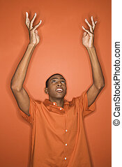 Man with arms raised. - Young African-American man throwing...