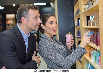 man with assistant help choosing beauty products at beauty shop