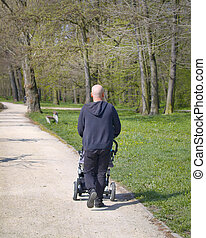 Man with baby stroller walks in spring park at morning