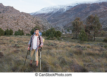 Fit young man with backpack and trekking poles walking on forest landscape