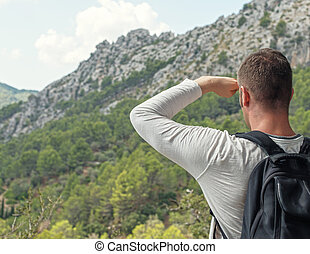 Man with backpack enjoying view in mountains.