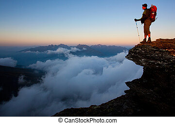 Man with backpack high above the misty mountain valley