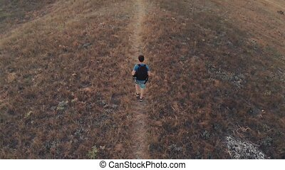 Man with backpack hiking aerial view - Man traveling with...