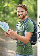 man with backpack holding a map