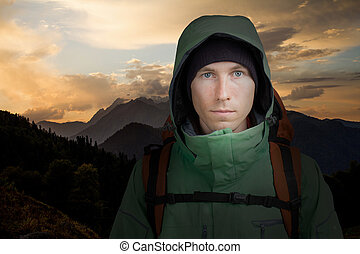 Man with backpack on the background of mountain sunset. Hiking.
