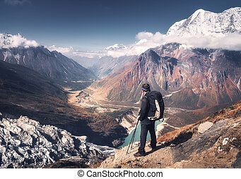 Man with backpack on the mountain peak at sunset