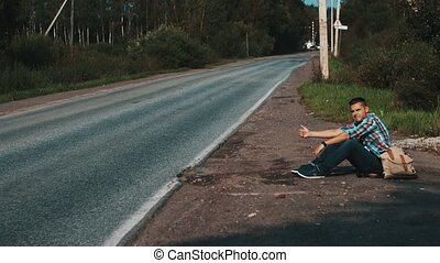 Man with backpack sitting at road in countryside. Hitchhiking. Thumb up. Travel