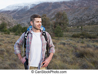 Man with backpack standing on fores