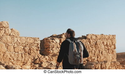 Man with backpack steps on ancient walls ruins. Caucasian...