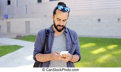 man with backpack texting on smartphone in city