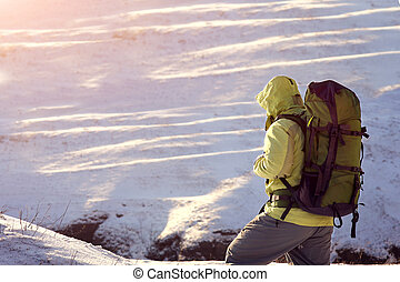 Man with backpack trekking in mountains. Cold weather, snow...