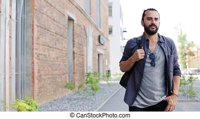 man with backpack walking along city street 18 - travel,...