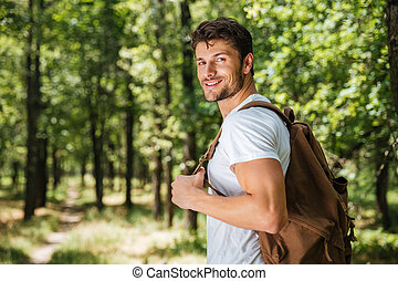 Man with backpack walking in forest