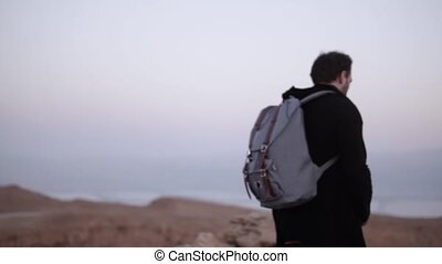 Man with backpack walks in desert. Slow motion. Young male wanders alone in dusk wilderness. Scenic mountain sky. Israel
