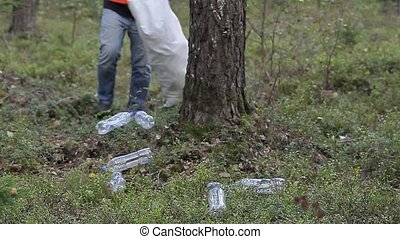 Man with bag picking up used plastic bottles in forest