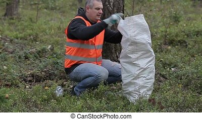 Man with bag picking up used plastic bottles