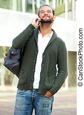 Man with bag talking on cell phone outside