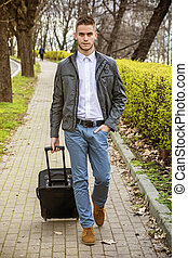 Man with baggage standing on pavement near river