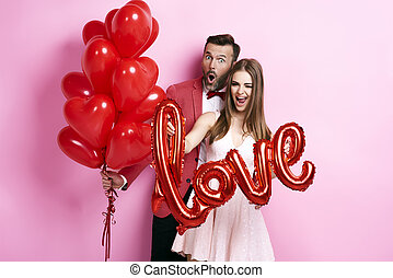 Man with balloon embracing his girlfriend