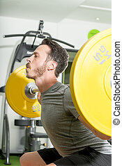 Man with Barbell on Shoulders Performing Squats in Gym