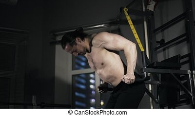 Man with bare torso doing push ups on parallel bars