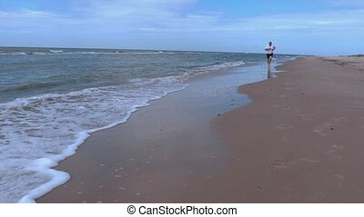 Man with barefoot running along the sea
