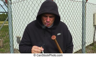 Man with baseball bat smoking near fence