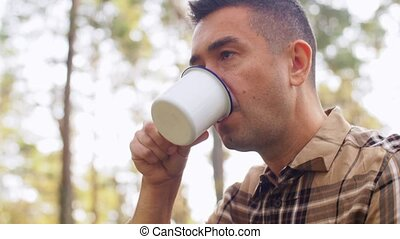 man with basket of mushrooms drinks tea in forest - picking ...