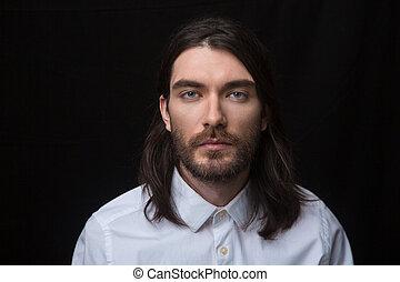 Man with beard and long hair looking at camera