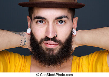 Close up portrait of a trendy young man with beard and piercings