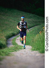 Man with beard athlete running in the mountains during a workout