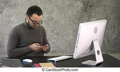 Man with beard, he is sitting at a black table, looking at his smartphone with his computer in front of him.