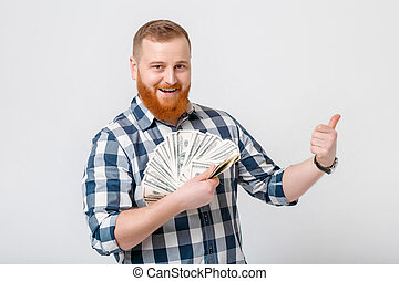 man with beard holding lot of hundred-dollar bills