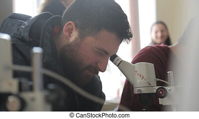 Man with beard looking into optical microscope screwing up his one eye.
