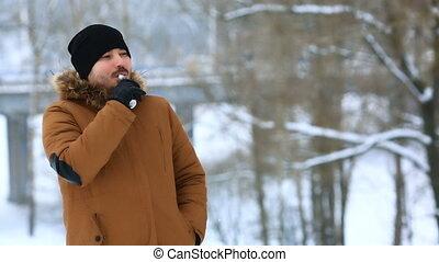 Man with beard smoke electronic cigarette outdoor. - Man...