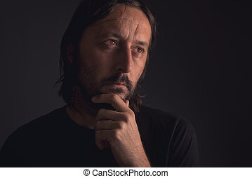 Man with beard thinking, low key portrait