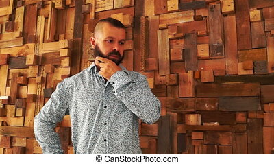 Man with beard thinking near wall from wood.
