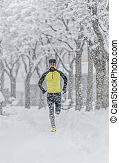 Man with beard trains by running in the snow in a cold winter