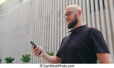 Man with Beard Wearing Glasses Using a Phone in Town - A man...