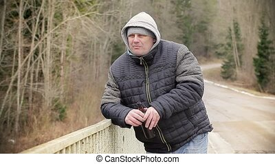 Man with beer bottle on the bridge
