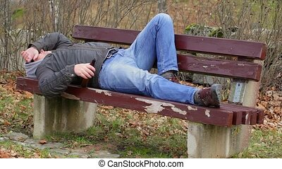 Man with beer bottle sleeping