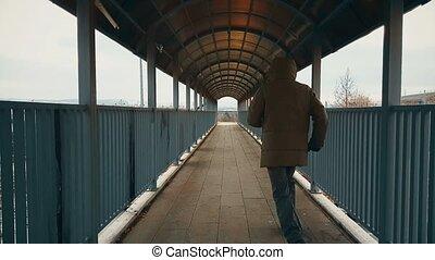 Man with beige coat running across the footbridge over highway
