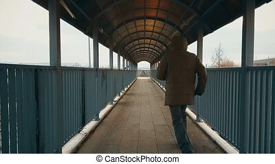 Man with beige coat running across the footbridge over highway