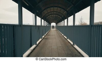 Man with beige coat walking across the footbridge over highway