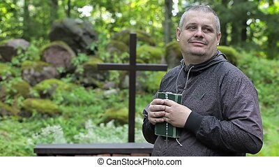 Man with Bible and rosary at outdoors church near cross