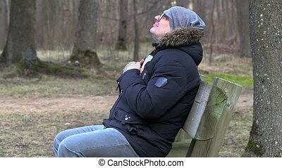 Man with Bible and rosary praying on bench in the park