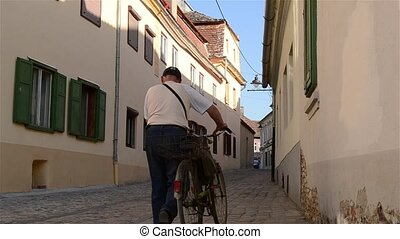 Man with Bicycle on Paved Street