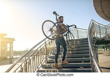 Man with bicycle on the city bridge