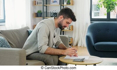 man with bills counting on calculator at home