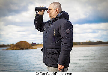 Man with binoculars at the lake